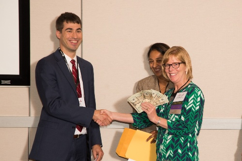 Dr. Catherine Marco [right] presents Dr. Garrett Bassett [left] with a cash prize for winning the Ohio EM Residents' Assembly Poster Competition for best case study
